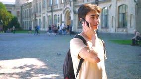 Ο αρκετά ασιατικός τύπος μιλά πέρα από το τηλέφωνο και εξετάζει τη κάμερα κατ' ευθείαν στεμένος κοντά στο πάρκο, υπαίθριος, ηλιόλ φιλμ μικρού μήκους