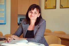 Ο αρκετά νέος δάσκαλος κάθεται με τα βιβλία στην τάξη Στοκ Εικόνες