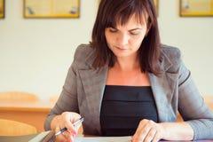 Ο αρκετά νέος δάσκαλος κάθεται με τα βιβλία στην τάξη Στοκ εικόνες με δικαίωμα ελεύθερης χρήσης