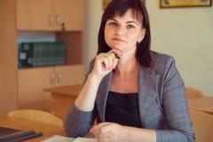 Ο αρκετά νέος δάσκαλος κάθεται με τα βιβλία στην τάξη Στοκ φωτογραφία με δικαίωμα ελεύθερης χρήσης