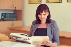 Ο αρκετά νέος δάσκαλος κάθεται με τα βιβλία στην τάξη Στοκ Φωτογραφία