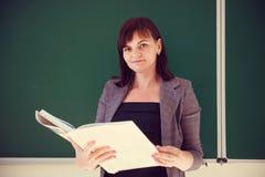 Ο αρκετά νέος δάσκαλος στέκεται με το βιβλίο κοντά στον πίνακα Στοκ Εικόνες