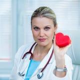 Ο αρκετά νέος θηλυκός γιατρός παρουσιάζει κόκκινο πρότυπο καρδιών σε Ambul Στοκ Εικόνες