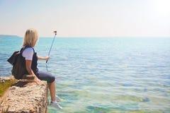 Ο αρκετά νέος τουρίστας γυναικών παίρνει selfie το πορτρέτο στην ακτή σε ένα ηλιόλουστο κορίτσι ημέρας παίρνει τη φωτογραφία για  Στοκ εικόνα με δικαίωμα ελεύθερης χρήσης