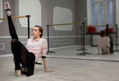 Ο αρκετά νέος χαριτωμένος χορευτής μπαλέτου θερμαίνει στην κατηγορία μπαλέτου Στοκ εικόνα με δικαίωμα ελεύθερης χρήσης