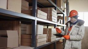Ο αρμόδιος εργαζόμενος σε ένα κράνος και τις φόρμες στέκεται δίπλα στα ράφια και αφαιρεί το κιβώτιο για το σωστό κατάλογο με την  απόθεμα βίντεο