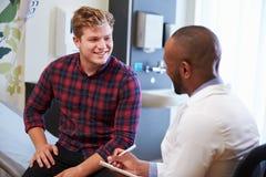 Ο αρσενικοί ασθενής και ο γιατρός διοργανώνουν τις διαβουλεύσεις στο δωμάτιο νοσοκομείων Στοκ εικόνα με δικαίωμα ελεύθερης χρήσης