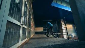 Ο αρσενικός έφηβος κάνει μια ακροβατική επίδειξη στο ποδήλατό του σε ένα κενό κτήριο απόθεμα βίντεο