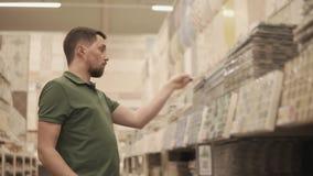 Ο αρσενικός αγοραστής εξετάζει την κεραμική κάλυψη τοίχων, απολαμβάνοντας τα σχέδια και σχετικά με φιλμ μικρού μήκους