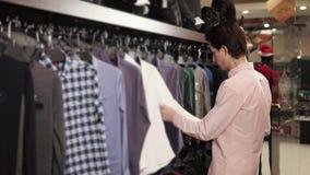 Ο αρσενικός αγοραστής επιλέγει τα πουκάμισα σε ένα κατάστημα σε μια λεωφόρο αγορών απόθεμα βίντεο