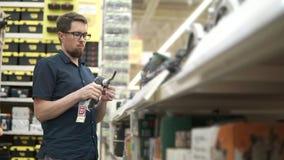 Ο αρσενικός αγοραστής παίρνει το ταλαντεμένος εργαλείο δύναμης σε ένα κατάστημα της οικοδόμησης των εργαλείων απόθεμα βίντεο