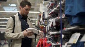 Ο αρσενικός αγοραστής προσέχει το ζευγάρι των πάνινων παπουτσιών σε μια περιοχή πωλήσεων στο αθλητικό κατάστημα απόθεμα βίντεο