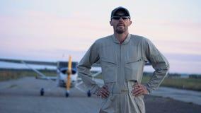 Ο αρσενικός αεροπόρος εγκαταλείπει biplane και τις στάσεις με ένα χαμόγελο απόθεμα βίντεο