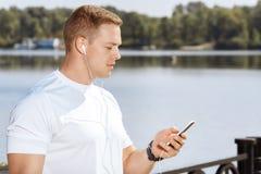 Ο αρσενικός αθλητής οργανώνει το τρέχοντας playlist του Στοκ εικόνες με δικαίωμα ελεύθερης χρήσης