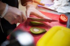 Ο αρσενικός αρχιμάγειρας παραδίδει τα γάντια κόβοντας το αβοκάντο Στοκ εικόνα με δικαίωμα ελεύθερης χρήσης
