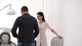 Ο αρσενικός ασθενής εισάγει ενός γιατρού, κάθεται στην καρέκλα Ο θηλυκός εύθυμος οδοντίατρος τον προσκαλεί για να καθίσει Νέα γυν απόθεμα βίντεο