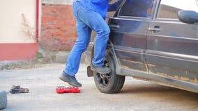 Ο αρσενικός αυτόματος μηχανικός με ένα γαλλικό κλειδί εξασφαλίζει μια ρόδα αυτοκινήτων απόθεμα βίντεο