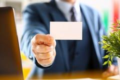 Ο αρσενικός βραχίονας στο κοστούμι δίνει την κενή τηλεπικοινωνιακή κάρτα Στοκ εικόνες με δικαίωμα ελεύθερης χρήσης