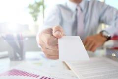 Ο αρσενικός βραχίονας στο κοστούμι δίνει την κενή τηλεπικοινωνιακή κάρτα στοκ εικόνες