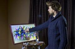 Ο αρσενικός γενειοφόρος καλλιτέχνης σε ένα σκοτεινό πουλόβερ σύρει μια καλλιτεχνική ζωή λουλουδιών ζωγραφικής βουρτσών ακόμα στο  Στοκ Εικόνα