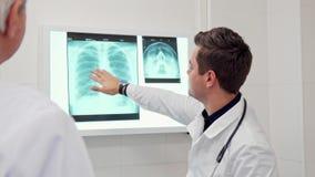 Ο αρσενικός γιατρός παρουσιάζει κάτι στην ακτίνα X στο συνάδελφό του απόθεμα βίντεο