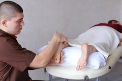 Ο αρσενικός γιατρός τρίβει τα πόδια του νέου κοριτσιού που βρίσκεται στον καναπέ στο bri Στοκ φωτογραφίες με δικαίωμα ελεύθερης χρήσης
