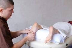 Ο αρσενικός γιατρός τρίβει τα πόδια του νέου κοριτσιού που βρίσκεται στον καναπέ στο bri Στοκ Φωτογραφίες