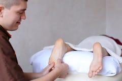 Ο αρσενικός γιατρός τρίβει τα πόδια του νέου κοριτσιού που βρίσκεται στον καναπέ στο bri Στοκ Εικόνα