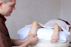 Ο αρσενικός γιατρός τρίβει τα πόδια του νέου κοριτσιού που βρίσκεται στον καναπέ στο bri Στοκ Φωτογραφία