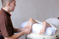 Ο αρσενικός γιατρός τρίβει τα πόδια του νέου κοριτσιού που βρίσκεται στον καναπέ στο bri Στοκ εικόνα με δικαίωμα ελεύθερης χρήσης