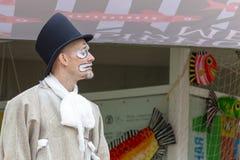 Ο αρσενικός δράστης στα φωτεινά ενδύματα και cilinder παίζει ένα meme σε ένα θέατρο οδών στοκ φωτογραφία με δικαίωμα ελεύθερης χρήσης