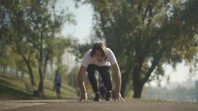 Ο αρσενικός δρομέας παίρνει μια χαμηλή έναρξη στο πάρκο απόθεμα βίντεο