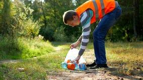 Ο αρσενικός εθελοντικός καθαριστής στην πορτοκαλιά φανέλλα σημάτων καθαρίζει τα απορρίματα στο δάσος, που καθαρίζει το δάσος και  απόθεμα βίντεο