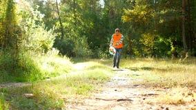 Ο αρσενικός εθελοντικός καθαριστής στην πορτοκαλιά φανέλλα σημάτων καθαρίζει τα απορρίματα στο δάσος, που καθαρίζει το δάσος και  φιλμ μικρού μήκους