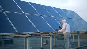 Ο αρσενικός ειδικός στα ενδύματα προστασίας καθαρίζει ένα ηλιακό πλαίσιο εναλλακτικός ανασκόπησης ηλιακός αέρας ενεργειακής απεικ απόθεμα βίντεο