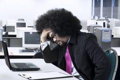 Ο αρσενικός επιχειρηματίας αισθάνεται τον πονοκέφαλο στον εργασιακό χώρο Στοκ φωτογραφίες με δικαίωμα ελεύθερης χρήσης