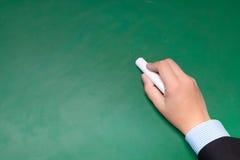 Ο αρσενικός επιχειρηματίας παραδίδει το κοστούμι γράφοντας σε έναν πίνακα με το λευκό Στοκ Εικόνες