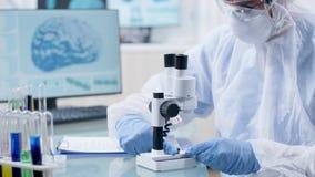 Ο αρσενικός ερευνητής στη φόρμα βάζει ένα δείγμα κάτω από το μικροσκόπιο απόθεμα βίντεο
