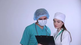 Ο αρσενικός ιατρικός σύμβουλος με το νέο θηλυκό γιατρό εξετάζει το φιαλλίδιο απόθεμα βίντεο