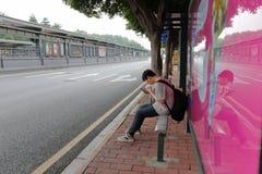 Ο αρσενικός κάτοχος διαρκούς εισιτήριου κάθεται στη στάση λεωφορείου στοκ εικόνα