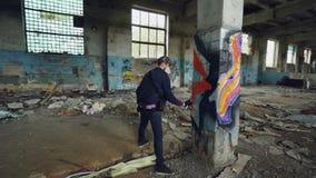 Ο αρσενικός καλλιτέχνης γκράφιτι διακοσμεί την παλαιά χαλασμένη στήλη μέσα στο κενό βιομηχανικό κτήριο με τις αφηρημένες εικόνες  απόθεμα βίντεο