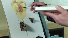 Ο αρσενικός καλλιτέχνης easel σύρει ένα λουλούδι εκτός από μια πεταλούδα κάθεται 4k φιλμ μικρού μήκους