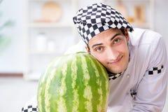 Ο αρσενικός μάγειρας με το καρπούζι στην κουζίνα Στοκ Εικόνα