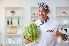 Ο αρσενικός μάγειρας με το καρπούζι στην κουζίνα Στοκ φωτογραφία με δικαίωμα ελεύθερης χρήσης
