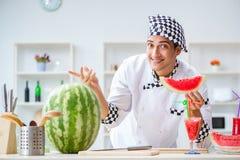 Ο αρσενικός μάγειρας με το καρπούζι στην κουζίνα Στοκ Φωτογραφία