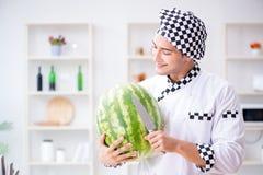 Ο αρσενικός μάγειρας με το καρπούζι στην κουζίνα Στοκ Εικόνες