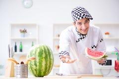 Ο αρσενικός μάγειρας με το καρπούζι στην κουζίνα Στοκ Φωτογραφίες