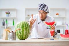 Ο αρσενικός μάγειρας με το καρπούζι στην κουζίνα Στοκ εικόνες με δικαίωμα ελεύθερης χρήσης