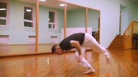 Ο αρσενικός μαχητής εκτελεί τα αρειανά τεχνάσματα με τα στοιχεία χορού στην αθλητική γυμναστική απόθεμα βίντεο