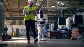 Ο αρσενικός μηχανικός ανάβει ένα droid εργαζόμενος με μια ταμπλέτα απόθεμα βίντεο